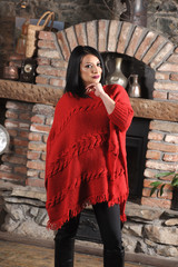 Pretty girl in red handmade knitted poncho with fries. Standing position at home
