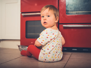 Little boy sitting by the stove in kitchen