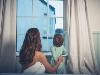 Mother with little boy looking out window in the morning