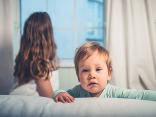 Little boy in bedroom with mother looking out the window
