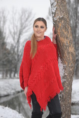 Pretty girl in red handmade knitted poncho with fries. Standing