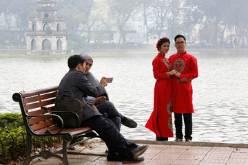 "A couple, wearing Vietnamese traditional long dress ""ao dai"", pose for wedding photo at Hoan Kiem Lake in Hanoi"