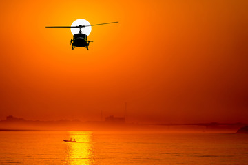 Wall Murals Helicopter silhouette of helicopter with sunset.