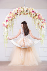 Beautiful bride in wedding dress in the interior sits on a hanging circle in floral arrangements on a white background