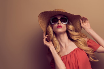 Wall Mural - Sensual Beautiful Woman in Vintage Trendy Sunglasses. Fashionable Wavy Hairstyle, Glamour Blond Lady in Summer Stylish fashion Dress. Young Playful Model Girl, Art Studio Portrait