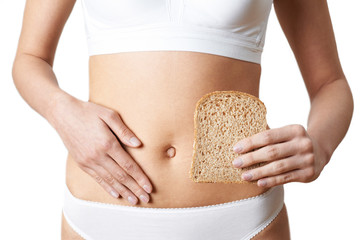 Close Up Of Woman Wearing Underwear Holding Slice Of Brown Bread And Touching Stomach