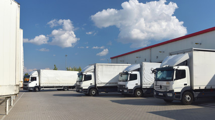 LKW´s am Depot einer Spedition werden beladen für den Transport von Waren in der Logistikbranche //  Trucks at the depot of a forwarding agency are loaded for the transport of goods