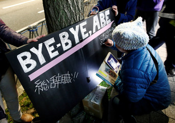 A protester writes a slogan on a board at a rally in Tokyo