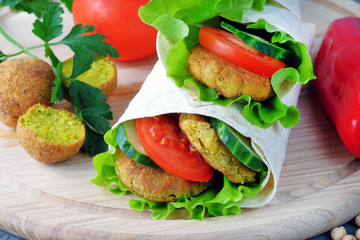 Falafel and vegetables wrapped in lavash on a light cutting board. Close-up view.