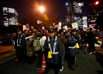 Policemen stand next to protesters holding banners denouncing Japanese Prime Minister Shinzo Abe at a rally in Tokyo