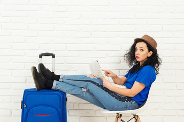Stylish girl in hat sitting with blue suitcase before trip.