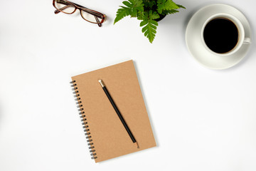Cup of coffee with notebook on white desk, Top view, copy space