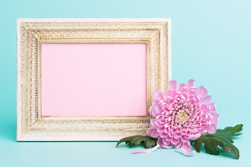Happy Mother's Day, Women's Day, Valentine's Day or Birthday Pastel Candy Blue Coloured Background. Bright pink flower on a table with empty picture frame greeting card.