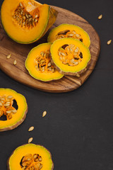 Delicious fresh pieces of ripe pumpkin on wooden background