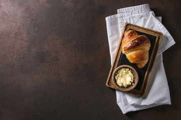Fresh baked traditional croissant on wooden slate serving board with butter on white cloth napkin over dark brown texture background. Top view, space