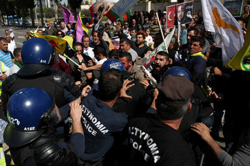 Kurds living in Cyprus scuffle with riot police officers during a demonstration against the Turkish offensive on Kurdish forces in northwest Syria, outside the Russian Embassy in Nicosia