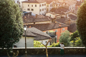 Man enjoys the view of ancient medieval italian city Barga, Tuscany, Italy. Picturesque european travel destination concept.