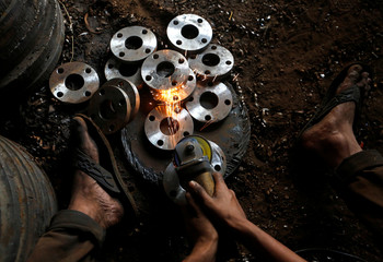 A man works inside a workshop in an industrial area in Mumbai