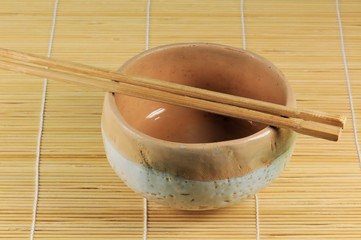 Japanese traditional cup with sticks on vegetable mat.