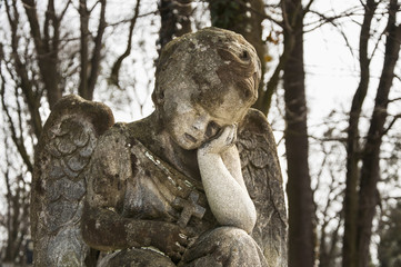 An old stone statue.  An angel cries over the child's grave (religion, Christianity, faith concept)