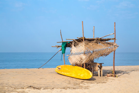 Yellow surf board and hut on sandy beach in Goa, India.
