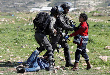 Israeli border policemen hold back a medic as detained Palestinian lies on the ground during clashes near the Jewish settlement of Beit El, near Ramallah