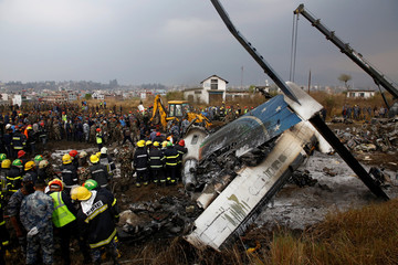 Rescue workers work at the wreckage of a US-Bangla airplane after it crashed at the Tribhuvan International Airport in Kathmandu