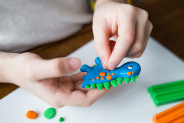 Creative kid molding at home. child play with plasticine. child sculpts a dinosaur