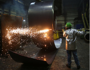 A worker cuts a steel coil at the Novolipetsk Steel PAO steel mill in Farrell, Pennsylvania
