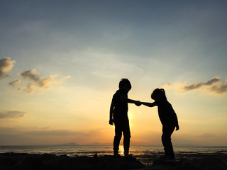 Silhouette of two sibling playing together at the beach on sunset