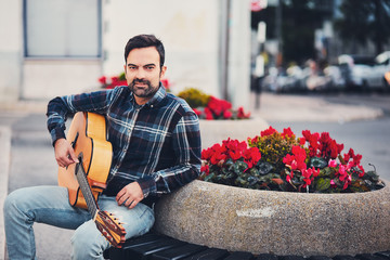 Stylish man with beard in a plaid shirt and jeans in the street near a park with flowers and a guitar in his hands. Macho with a beautiful smile sits in the evening on the bench and plays the guitar.