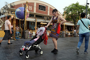 A woman pushes her baby cart at Asiatique The Riverfront in Bangkok