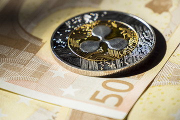 Cryptocurrency coins over euro banknotes; Ripple coin