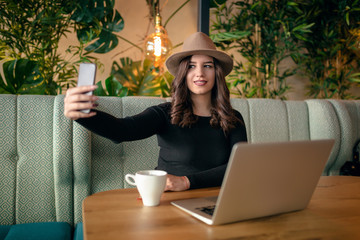 Selfie time. Portrait of styled beautiful girl with hat and black dress taking selfie while drinking coffee in cafe.