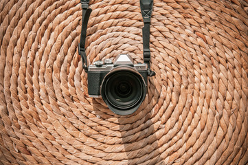 Old vintage retro style camera on dried water hyacinth mat natural texture background