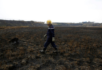 A firefighter walks along the burned field after the crash of US-Bangla airplane at Tribhuvan International Airport in Kathmandu
