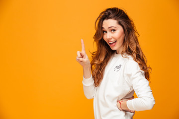 Happy brunette woman in sweater posing with arm on hip