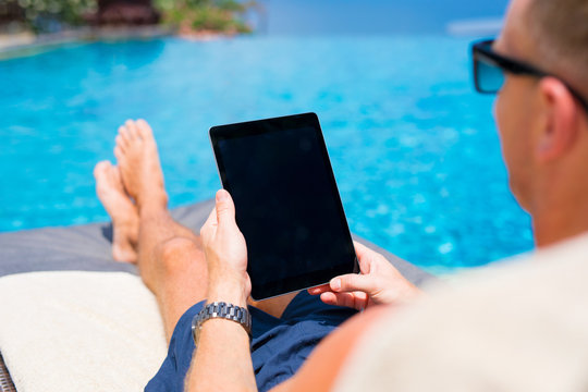 Man looking at tablet computer while sunbathing by the pool.
