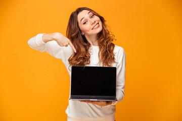 Pleased brunette woman in sweater showing blank laptop computer screen Wall mural