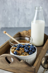 Homemade granola in a white bowl on the wooden tray with a bottle of milk and honey. Food Photography of a healthy morning breakfast.