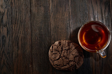 Cup of tea with a couple of chocolate cookies on a wooden background, top view, selective focus