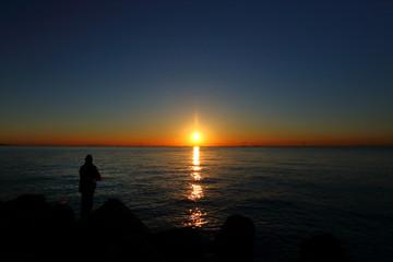 日の出は背景に東京の海で釣り