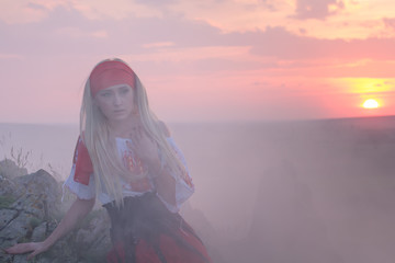 Beautiful young blonde girl with a red scarf, a traditional romanian blouse and a red and black skirt covered in smoke at sunset, Romania