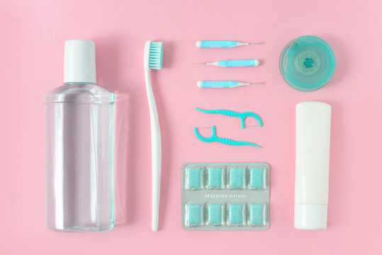 Toothbrushes, toothpaste, rinse and chewing gum set on pink background. Dental and healthcare concept. Free copy space.