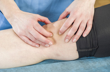 Physiotherapist, chiropractor doing a patellar mobilization, Knee pain. Spraining torn ligaments