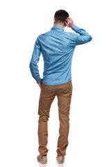 back view of a man scratching his head and thinking