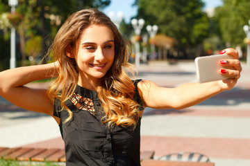 Portrait of young beautiful smiley woman making selfie outdoors in park