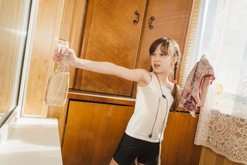 Little girl with pigtails, with headphones, with rag and spray does wet cleaning on balcony.