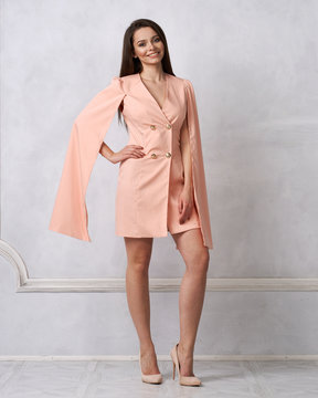 Attractive brunette female model wearing mini pink dress with golden buttons, split, long hanging sleeves and heeled shoes posing against white wall on background. Beautiful woman in trendy outfit.