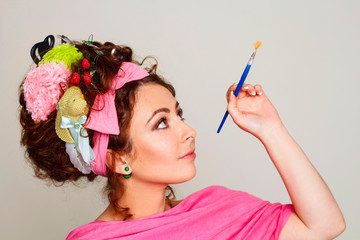Portrait of young and funny woman artist with paintbrush wearing interesting and creative hairstyle